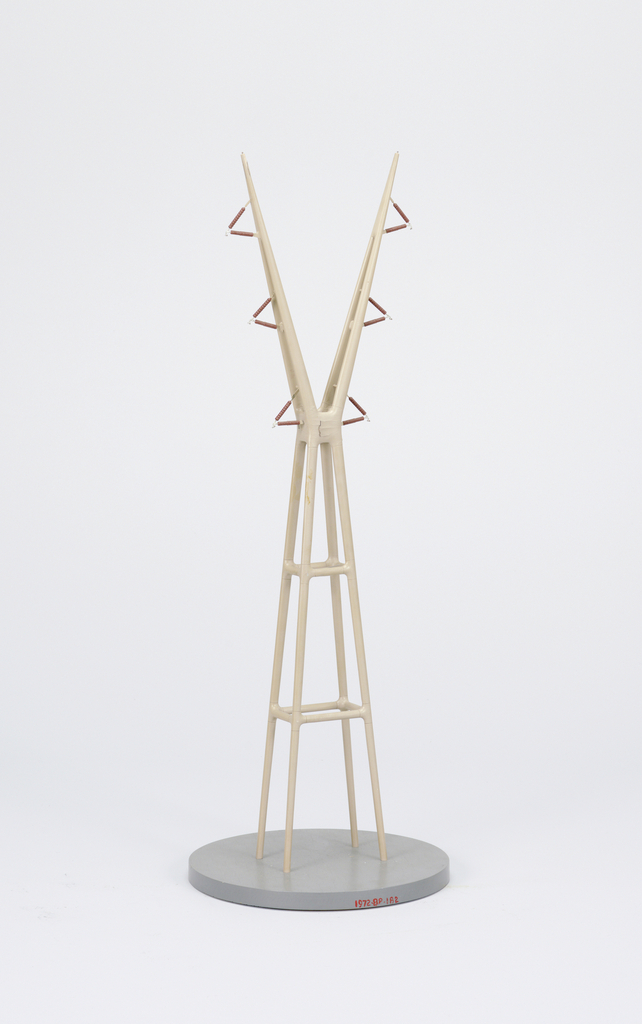 "A model of a high-voltage transmission tower. It is made on a circular base with tall four legged tower with two long arms on the top in the shape of a ""Y""."
