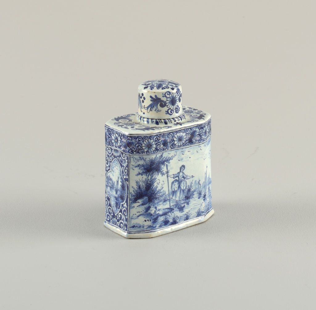 Rectangular body with champfered corners; straight-sided circular neck, flat-topped cover; painted in underglaze blue on white on 2 sides with fig-ures, on the shorter sides with reserves of sailboats on floral pattern background, floral band around top body; cover painted with floral motifs.