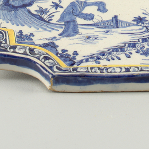 Shaped plaque with raised molded border and circular ribbed hanging loop on top edge; painted in underglaze blue and yellow with leaf scroll border, chinoiserie scene center with figure in landscape.