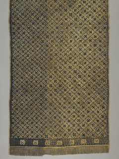 Large sarong (kain panjang), batik in dark blue, showing diamond-shaped all-over pattern. Small border band on either side showing a grid-work pattern interrupted by squares. Piece painted with gold (prada technique) in lower regions leaving top free for handling and folding.
