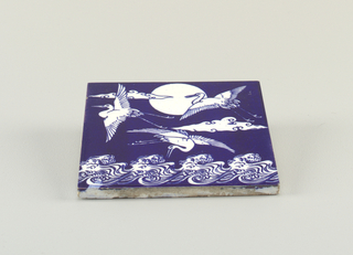 A blue and white earthenware tile with a painted scene of three birds flying over water.