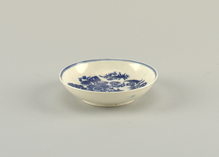 Round saucer on circular foot. Blue floral decoration at center. Double line on inner rim.