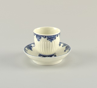 Cup circular, without handle; tall, with raised ribbing two- thirds of the way up its side. Saucer has curved sides, raised circular rim at centre with four breaks, and radiating raised ribs half way towards edges. Decorated with blue conventional pattern of foliage and scrolls about edges.