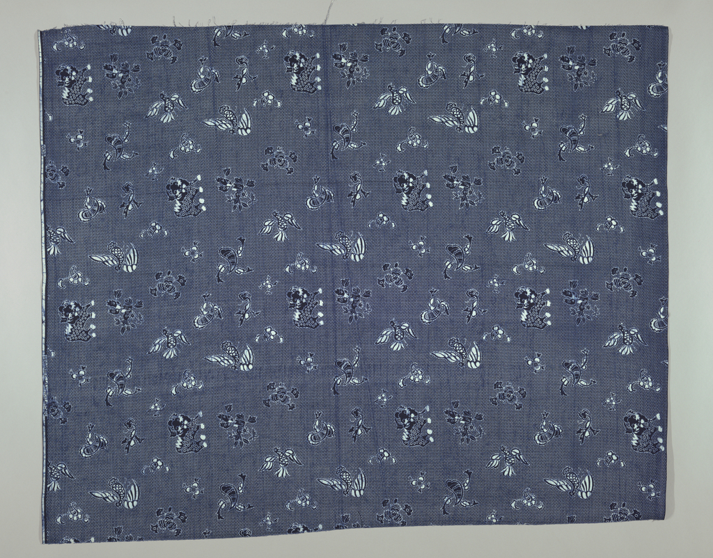 Imitation batik of wax printed cotton with a half drop repeat in dark blue and white of Indonesian style animal, bird and floral motifs on a dotted background.