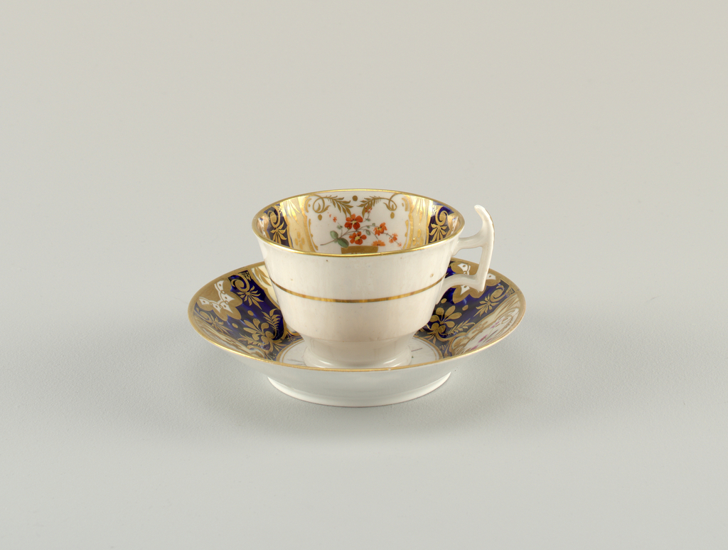 Cup has handle with raised spur. Exterior decorated with a slim gilded band. Saucer and cup interior with segmented decoration of gilt and enamel florals on alternating white and blue ground. Gilding at rim.
