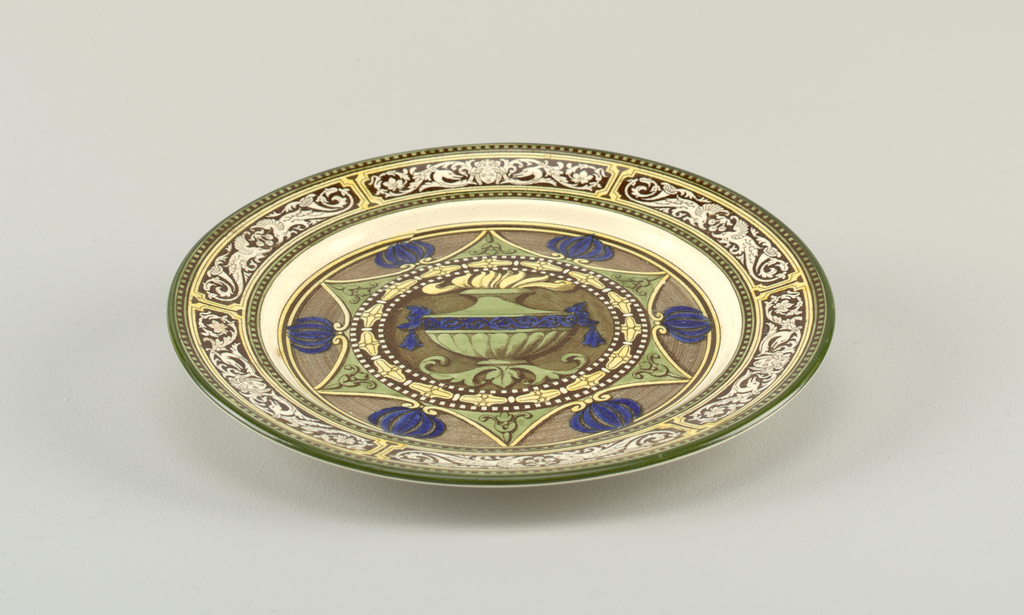 Plate with brown transfer print with hand-colored glaze in yellow, green and blue. Design shows flaming urn framed by geometric pattern. Grotesque border.
