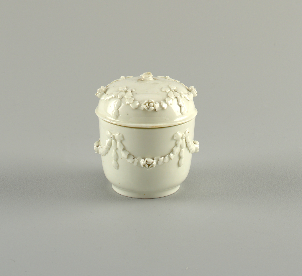 A) Circular box on small foot. B) Domed cover with narrow everted rim. Both box and cover decorated with applied leaves forming four swags, bows and roses. Large rose finial. No marks.
