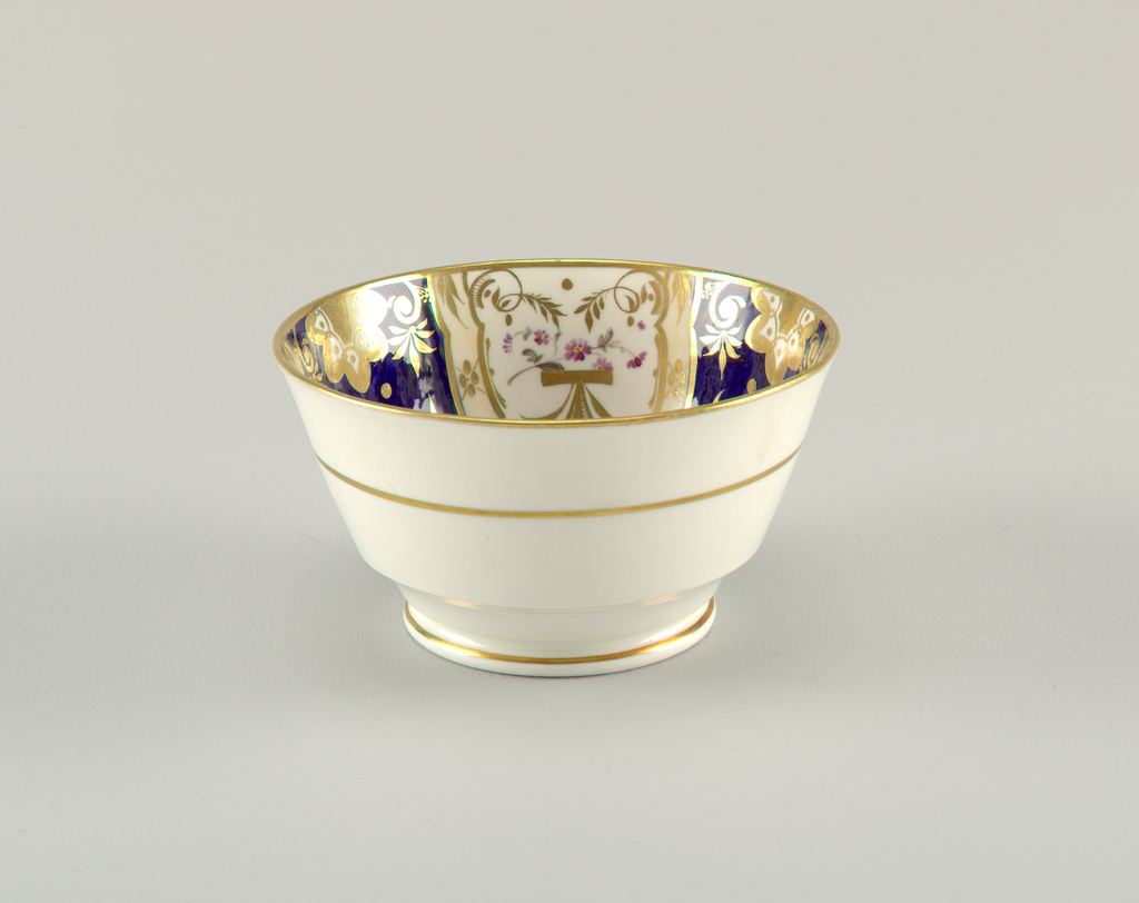 Footed bowl decorated with thin gilded bands. Interior shows segmented decoration of gilt and enamel florals on alternating white and blue ground. Gilding at rim.
