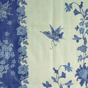 "A panel of glazed cotton, resist-printed, probably by a batik method known as cap (tjap) printing (wax resist applied by means of blocks inlaid with copper strips). Design is dark blue, light blue, and white, showing a butterfly hovering over full twining bouquet of flowers (""buketan"" motif). Border is floral (a North Javanese batik innovation) with repeat in two shades of blue covering two thirds of piece (the body or 'badan' of the sarong); design on the remaining third (the head or 'kepala' ) is in two shades of blue on dark blue ground. The leaves of flowers and foliage, as well as the wings of butterflies, are filled with small white dots and lines."