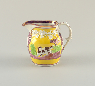 Embossed decoration on pitcher. Hounds in purple, yellow and white landscape. Beneath spout and loop, feathered handle, a shell framed with purple. Open spout and rimmed with metallic purple.