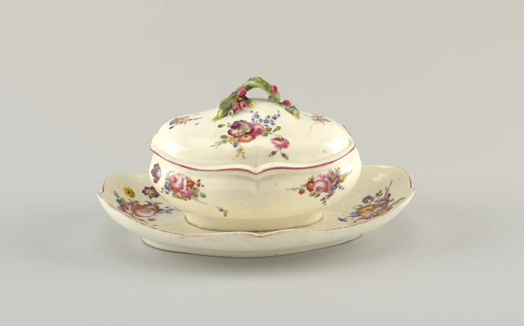 Tray attached to bowl, oval with shaped edges; bowl rounded, with shaped edges which are repeated in contour of domed cover. Cover has handle in form of an olive branch with leaves and olives, and notch for ladle. Decorated with sprays of flowers.