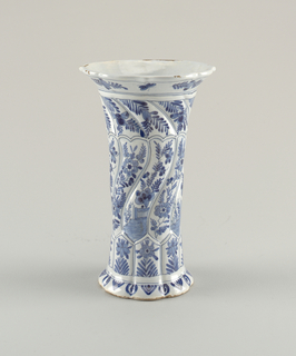 Tall, twisted, fluted eight-sided vase with short flared foot and flaring mouth with shaped rim; painted in underglaze blue on white with eight vertical panels each with flower bottom, alternate mid-sections of landscapes or flowers, top section of flowers.