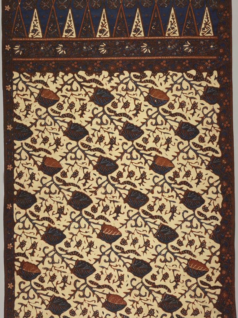 """Long, coarse cotton panel, probably a sarong, in rust, blue, and dark brown on cream ground. Two foliage borders followed by the head or 'kepala' of the piece with two rows of isosceles triangles facing each other (""""tumpal"""" motif), then two-thirds of length (the body or 'badan') filled by stylized, diagonally-moving leaf and flower pattern."""