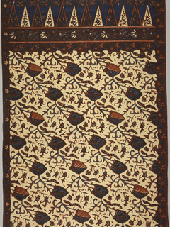 "Long, coarse cotton panel, probably a sarong, in rust, blue, and dark brown on cream ground. Two foliage borders followed by the head or 'kepala' of the piece with two rows of isosceles triangles facing each other (""tumpal"" motif), then two-thirds of length (the body or 'badan') filled by stylized, diagonally-moving leaf and flower pattern."