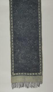 "Long, narrow shoulder cloth (selendang) or sash in dark indigo-blue and light blue-gray. Field is a continuous pattern dominated by the ""sawat"" or ""mirong"" motif (wings of Garuda, mount of Vishnu) and small individual blossoms. Border is a continuous floral vine with a squared blossom in each corner. Imitating fringe (10.5cm) and warp fringe (6-7cm) at both ends."