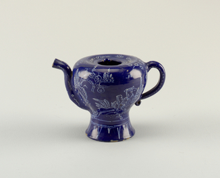 "Inverted pear-shaped body on a high foot. Tube-shaped spout, similar to those found on posset-pots. Loop handle with lower scroll. Decorated in the ""bleu-persan"" style, with white chinoiserie figures on a cobalt glue ground. Buff clay revealed in chips."