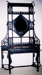 Large, cast iron frame, rectangular in shape, composed of top mirrored section and table-like base. Top section has oval mirror at center, with two rows of six hooks either side; iron framework ornamented with molded and pierced oriental stylized leaf motifs, two dog-like figures at top corners, and turkey head top edge of mirror. Base has inset marble top, central drawer with projecting brass(?) knob. Removable trays lower sides with curved supporting rail above. Stretcher at base. Ironwork ornamented with stylized leaf patterns, as top section.
