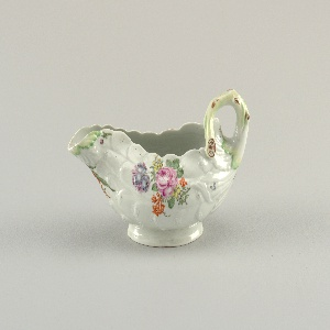 White porcelain leaf-shaped sauce boat with a branch handle.  Decorated with small flower details.