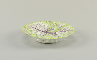 Round dish in the form of lettuce leaves with holes throughout, pink midribs and veins, and green edges.