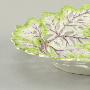 Round dish in the form of reticulated lettuce leaves with holes throughout, pink midribs and veins, and green edges.