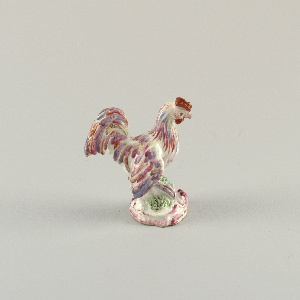 Polychromed figure of a rooster on a rocaille pedestal.