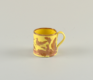 Cylindrical form with loop handle; yellow ground with pink copper luster decoration of bird sitting on branch above foliage; luster band at mouth. Yellow interior.