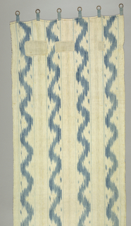 Vertical curtain panel with four broad vertical bands; each filled with a single broad serpentine band in shaded blue with a small blaze in each scallop and with a straight narrow pale blue stripe on each side. All formed by blue ikat in the warp direction.