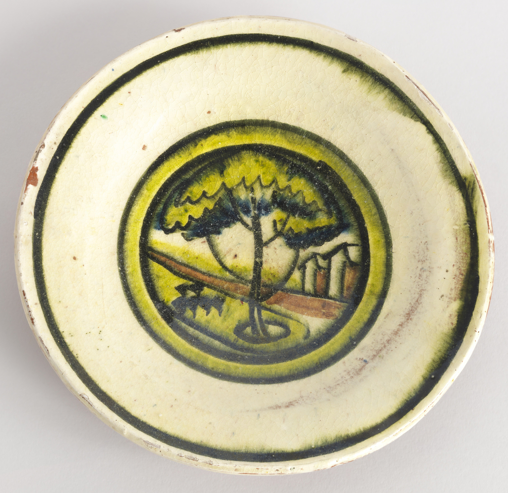 Circular plate decorated with stylized landscape with tree and houses in palette of yellow, green, brown and black on white ground, the scene within bands of black and mottled green and yellow;  very wide rim with thin black band.