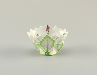 Dish in the form of overlapping leaves. The upper leaves are left undecorated; the lower leaves are painted with pink veins and green edges. Interior is smooth with painted florals.