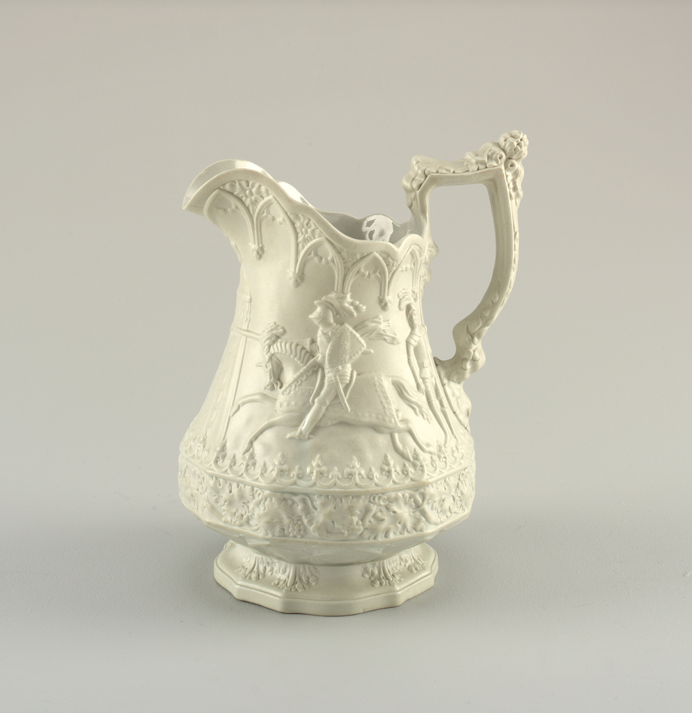 A highly decorative white jug with detail on the body, spout and handle. The center depicts a knight riding a horse in an outdoor scene.