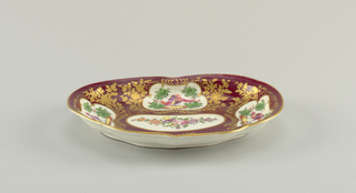 Kidney-shaped dish. Maroon ground with white reserves filled with birds and flowers. Floral gilt decoration throughout.