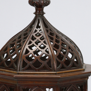 Octagonal form of wood and metal wire; ogee arches springing from clustered columns on the eight corners; one side with hinged door. Ogee domed top with pierced imbrication and leafy finial. Bottom of sheet metal. Two perches and a swing in interior.