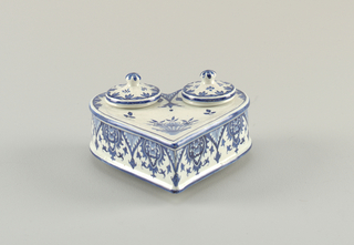 Heart shaped, horizontally placed on three small feet. Openings in two lobes, with two inkwells, each with cover. Slight depression on top, at point. Decoration of stylized flowers and foliage.