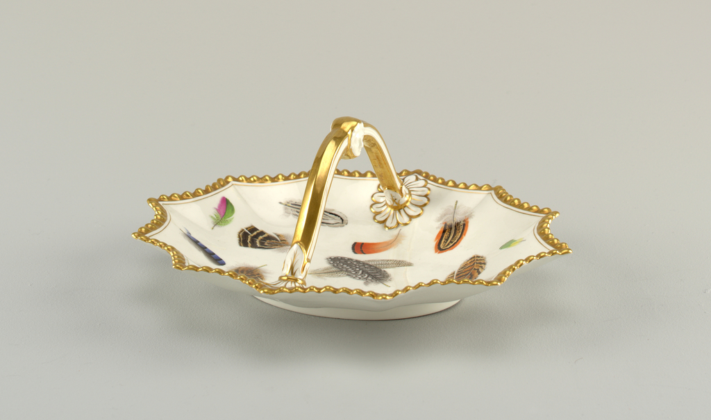 12-sided basket   with scalloped edges. Gilded handle terminating in rosettes. Center decorated with representations of various brightly-colored feathers.