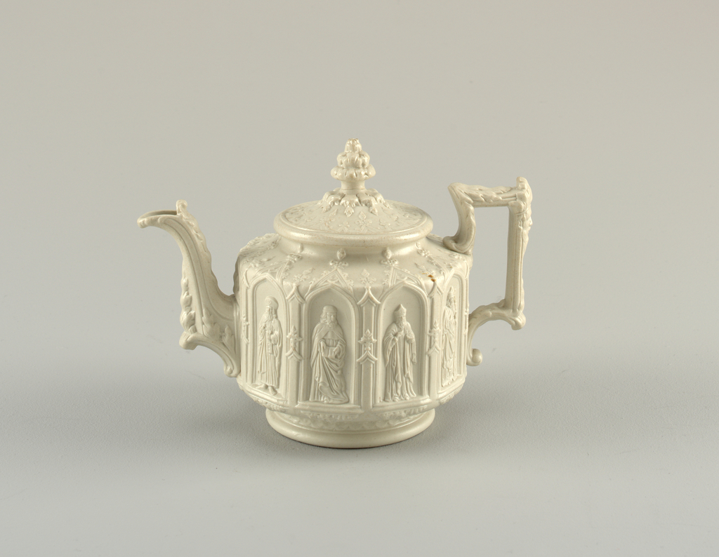 A highly decorative white teapot and lid with detail on the body, spout and handle. The center has panels depicting figures in an outdoor scene.