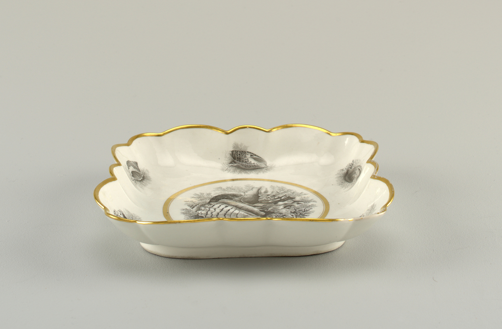 Square deep dish with fluted and scalloped edge. Overglaze printed decoration in black, of shells and seaweed. Gold medallion and border.