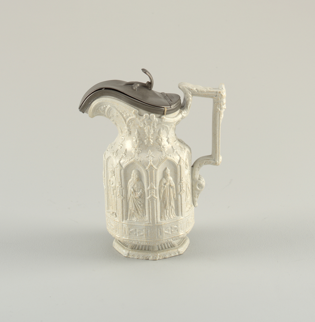 Highly decorative cream jug with detail on the body, spout and handle. The center has panels depicting figures in an outdoor scene. Jug has a hinged metal lid.