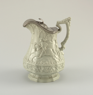 A highly decorative green jug with detail on the body, spout and handle. The center depicts a knight riding a horse in an outdoor scene. This jug includes a pewter cover.