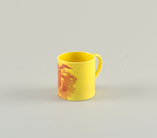 Cylindrical mug with red decoration on a yellow ground showing an eagle, its wings spread, above portrait ovals of Washington and Lafayette; strap handle.