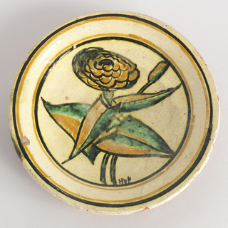 "Circular plate decorated with stylized image of a large flower and bud with broad leaves, in palette of yellow, green, black on white ground; white rim with black and yellow bands. ""HVP"" to lower right of flower stems."