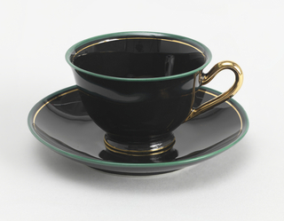 Wide slightly-flared cup with curved gold handle; cup's mouth is rimmed in turquoise with thin rim of gold at foot. Saucer in black with edge in turquoise and thin gold rim.