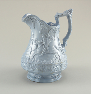 A highly decorative blue jug with detail on the body, spout and handle. The center depicts a knight riding a horse in an outdoor scene.