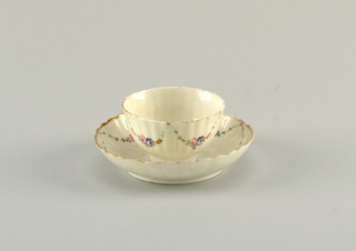 Tea bowl on high foot and a high-side saucer. Molded ribbing and scalloped edge. Overglaze polychrome floral swags. Gilding at rim.