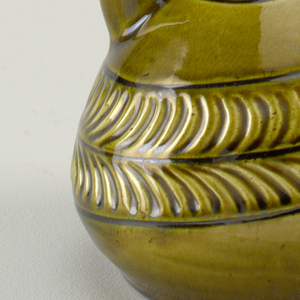 Stirrup-spout bottle with spiraling abstract decoration and green glaze.