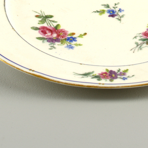 Circular, the rim scalloped and gilt.  Cavetto and border with small polychrome floral sprays on white ground; the border edged with narrow blue stripes interrupted by short diagonal strokes of gold, in pairs.  Glazed hole in foot ring.