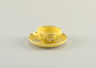 Yellow cup and saucer with upturned rims. Both decorated with metallic floral motif and band around rims.