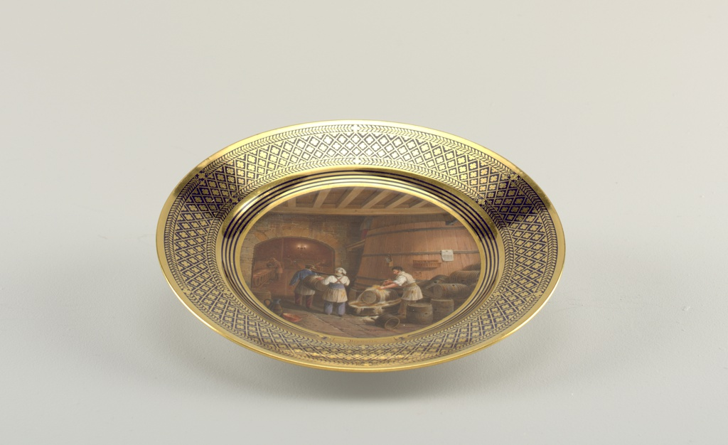 "Circular plate.  In center a polychromed scene of barrel washing, with inscription ""Brasserie / Etonnerie;"" gilt rim with deep blue diaper pattern."