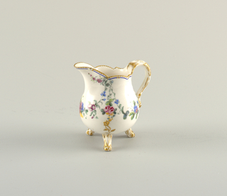 Pear-shaped with shaped mouth and lip; handle and three feet modelled and gilded in imitation of tree bark. Gilded floral spray in relief at points of junction of feet and handle with body. Painted floral swags in colors.