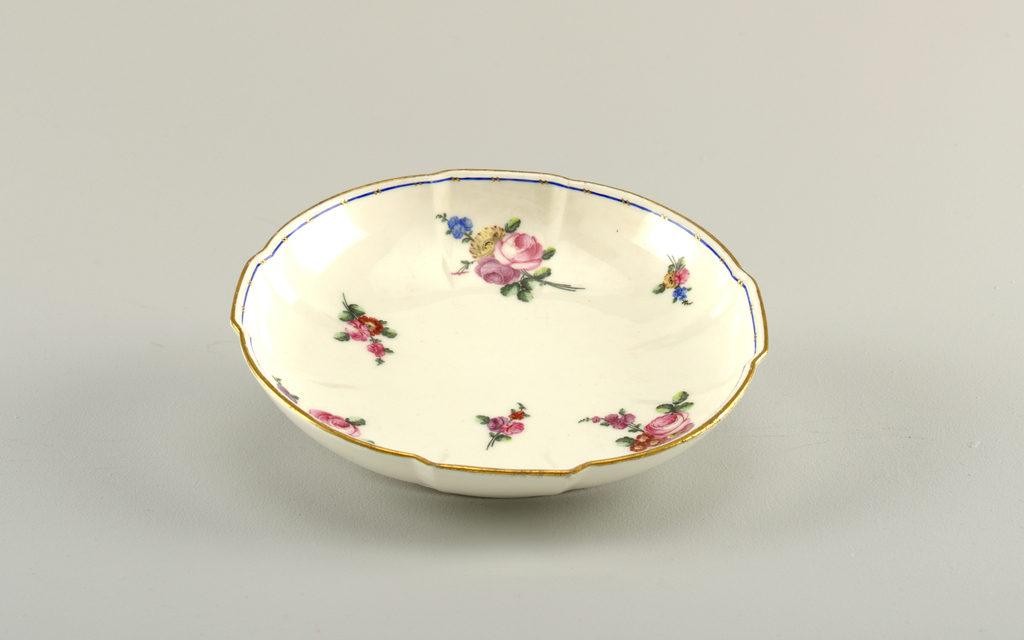 Round with four quadrant protrusions in sides. Decorated with floral sprays. Slim blue band on inside edge. Top edge gilded.