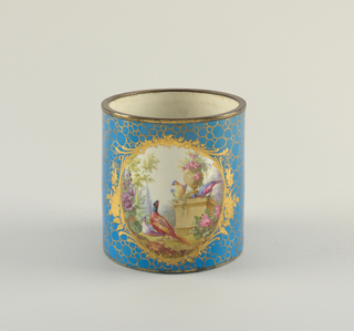 Cylindrical, with gilded brass strip at edge. Bleu céleste (sky blue) ground color with gilded pattern of circles. Gilded cartouches at front and back frame garden scenes with birds.